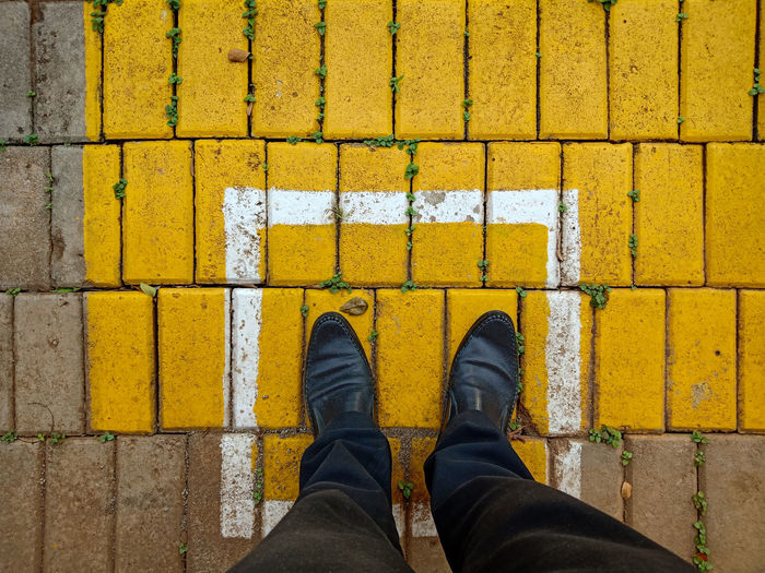 Low section of man standing on yellow street