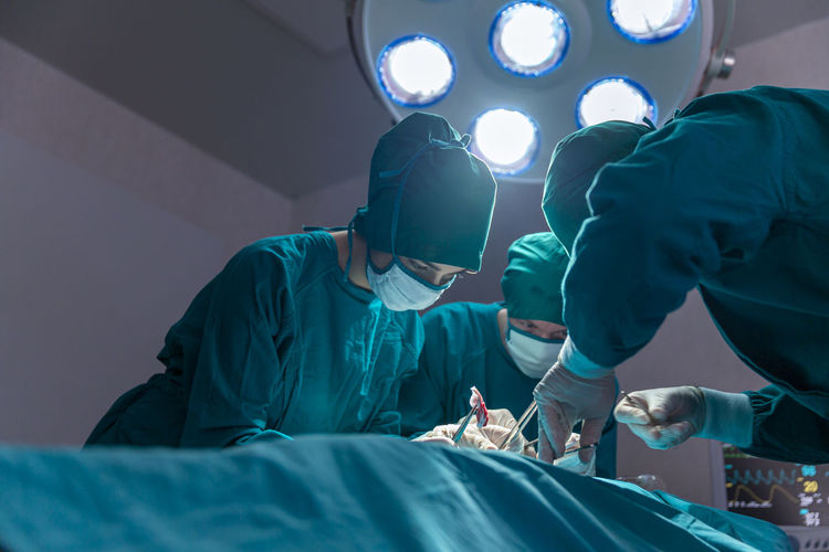 The surgeon team is working in the operating room. the surgeon is saving the patient's life.