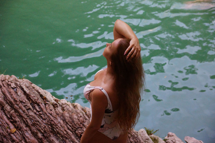 Woman wearing one piece swimsuit standing by lake
