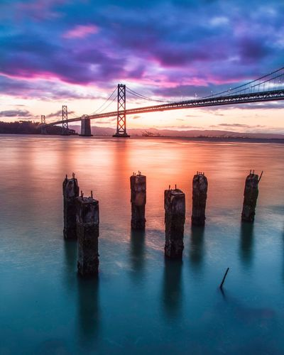 Oakland bay bridge against cloudy sky during sunset