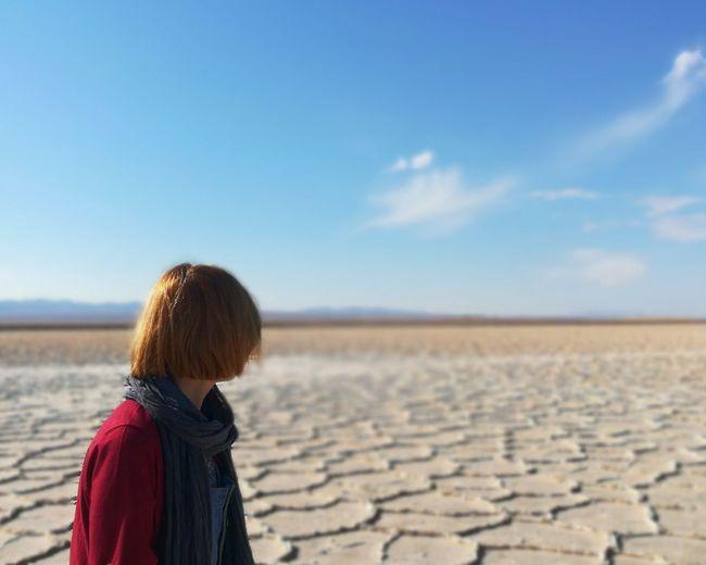 Woman on salt flat against sky