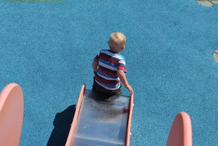 High angle view of baby boy playing on slide at playground