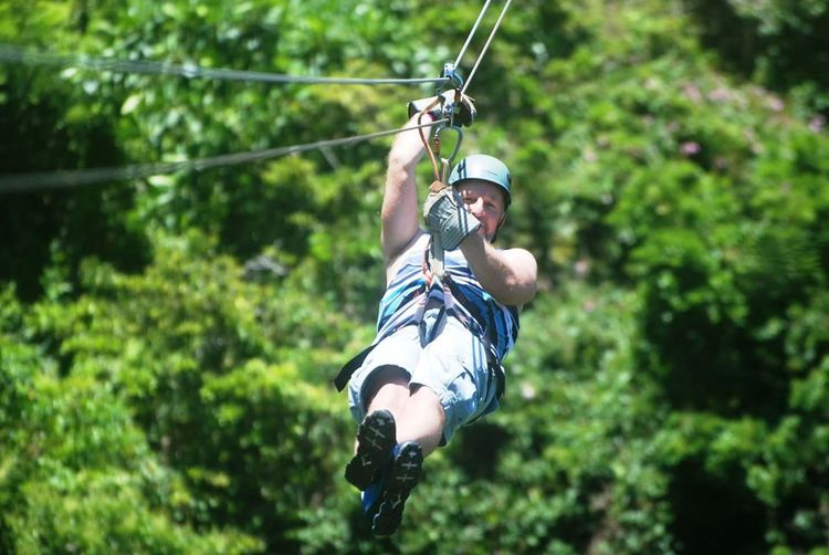 Man zip lining at forest