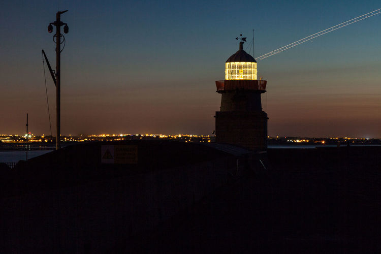 Silhouette of lighthouse at night
