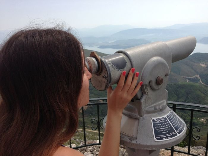 Close-up of woman looking at mountains through coin-operated binoculars