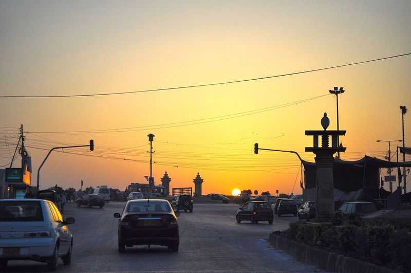 Cars moving on road against clear sky at sunset