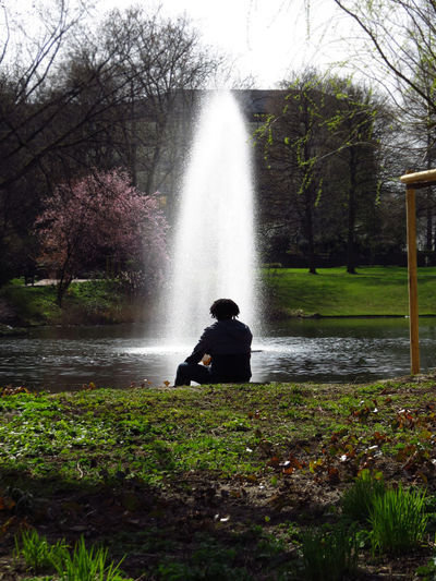 Adult Beauty In Nature Chilling Chilling In The Sun Enjoying Life Enjoying The Sun Fountain Nature One Person Outdoors Park Park - Man Made Space Park Life Parklife Parks People Pond Pondering Rear View Relaxing Relaxing Moments Sitting In The Park Sitting Outside Tree Water