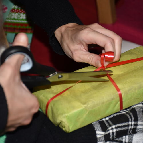 Cropped hand of woman cutting ribbon of gift on table