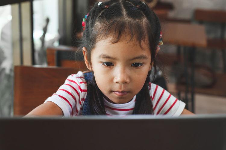 Schoolgirl Looking At Laptop In Classroom