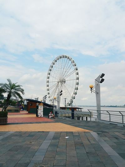 Ferris wheel by river in city against sky