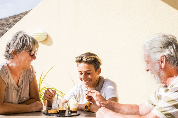 Family Having Dessert While Sitting At Table