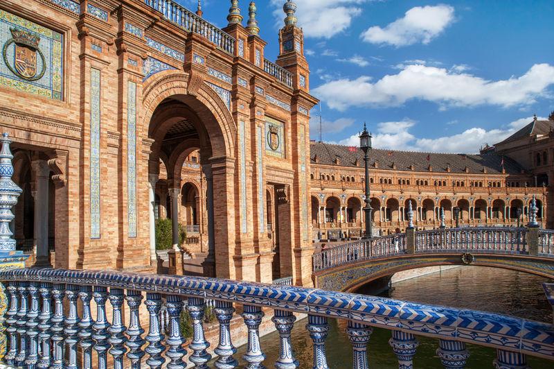 Arch bridges over canal outside plaza de espana against sky
