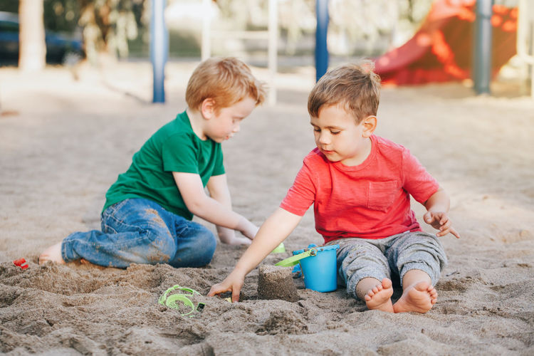 Boys playing with sand at playground