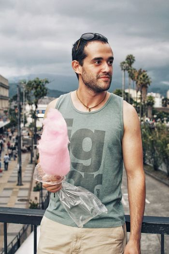 Man holding cotton candy while leaning against railing