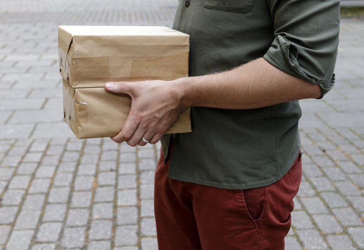 Midsection of man holding boxes