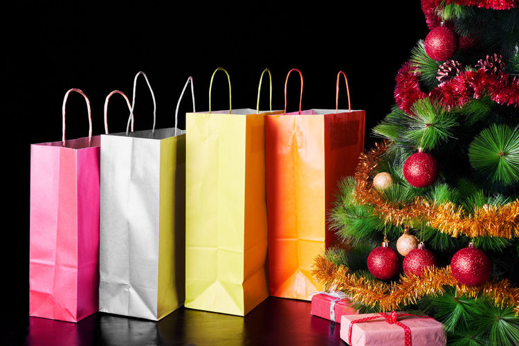 Close-up of shopping bags and christmas decorations over black background