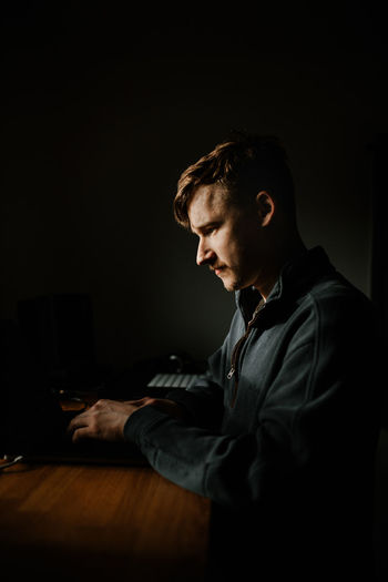 Young man using laptop in darkroom