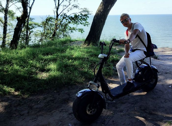 Full length of man sitting by sea on motor scooter