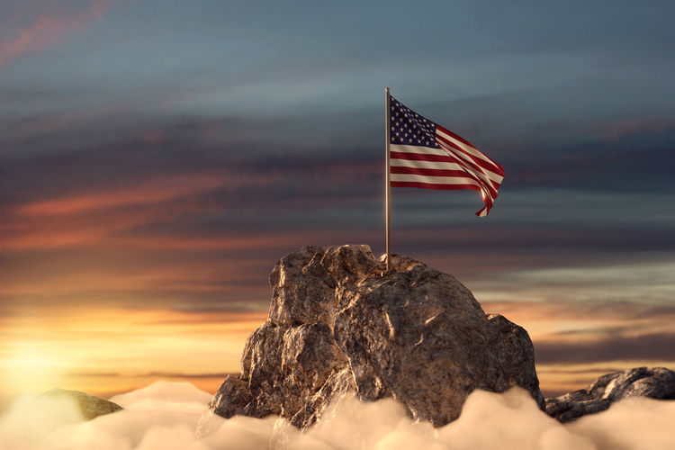Close-up of flag on rock against sky during sunset