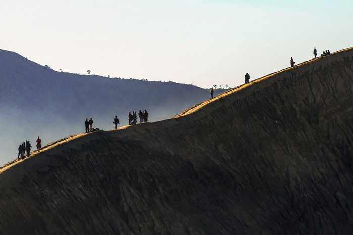 GROUP OF PEOPLE WALKING ON MOUNTAIN AGAINST CLEAR SKY