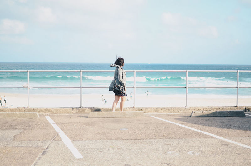 Side view of woman standing by railing against sea