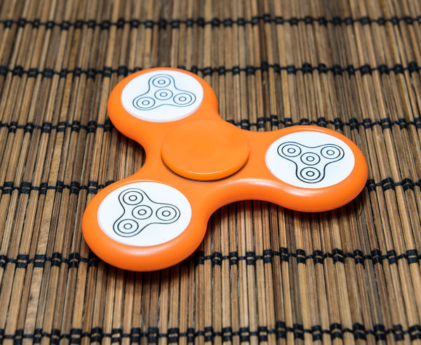 Fidget spinner stress relieving toy on bamboo mat background Bearing Children Closeup Fidget Spinner Fidgetspinner Focus Fun Game Hobbies Kids Latest Toy New Craze Plastic Play Spinner Toy Trend