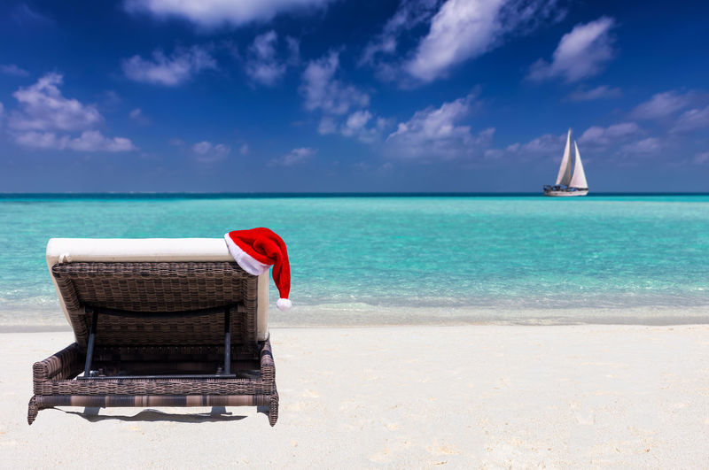 Santa hat on lounge chair at beach against blue sky