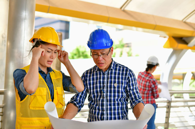 Analyzing ARCHITECT Architecture Asian  Background Blueprint Build Builder Business Businessman Businesspeople City Communication Construct Construction Cooperation Create Creator  Design Designer  Emotion Emotional Engineer Engineering Explaining  Female Helmet Industry Instrument Male Man Meeting Plan Planner Present Presentation Project Sad Sadness Strain Stress Stressful Talking Team Teamwork Tense Unhappiness Unhappy Woman Work