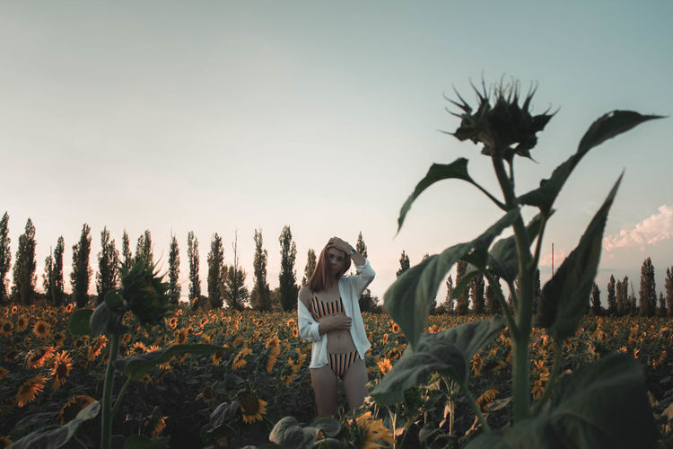 Woman Standing In Bikini At Sunflower Farm Against Sky