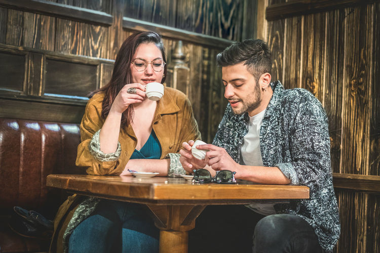 Young couple having a coffee in a wooden pub restaurant. Smiling Young Adult Table Real People Lifestyles Friendship Cafe Casual Clothing Young Women Couple - Relationship Two People Men Young Men Sitting Drink Togetherness Bonding Adult Happiness Positive Emotion Coffee Coffee - Drink Coffee Cup Coffee Time Coffee Break Espresso Wood - Material Public Transportation Restaurant Talking Relaxing Frienship Clothing Indoors