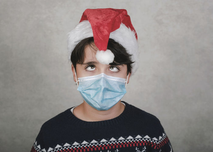 Close-up of boy wearing mask and santa hat standing against gray wall