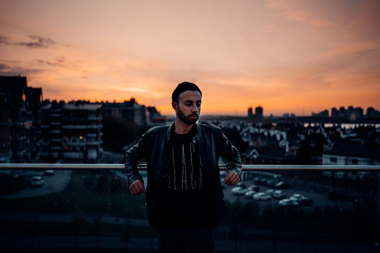 Portrait of man standing in city against sky during sunset