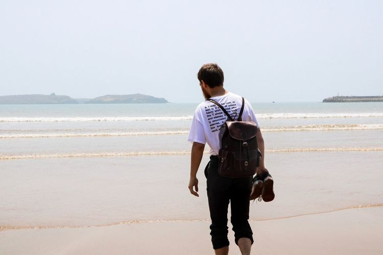 Rear view of man walking at beach against clear sky