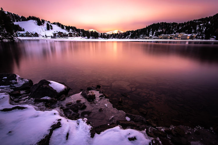 Copy Space Water Nature Lakeshore Sunrise Sky Tree Ice Winter Dawn Snow Frozen Rock Tranquility Lake Waterfront Beauty In Nature No People Tranquil Scene Non-urban Scene Cold Temperature Scenics - Nature Idyllic Pebble
