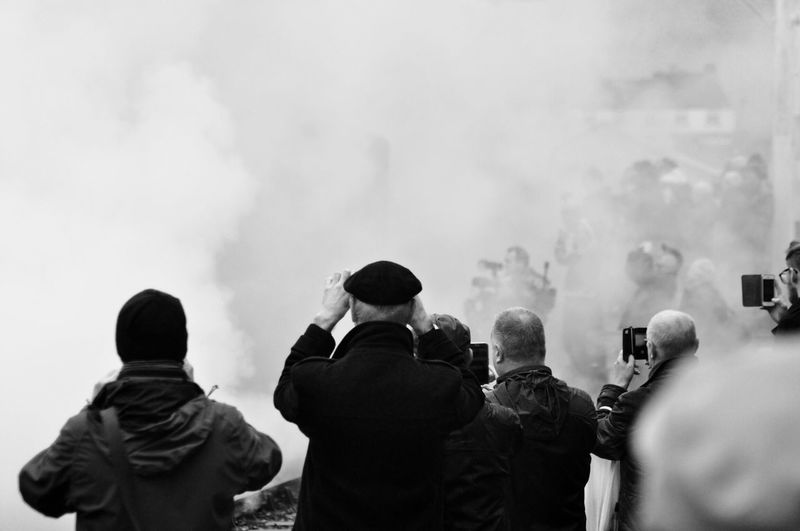 Rear view of people against sky with smoke