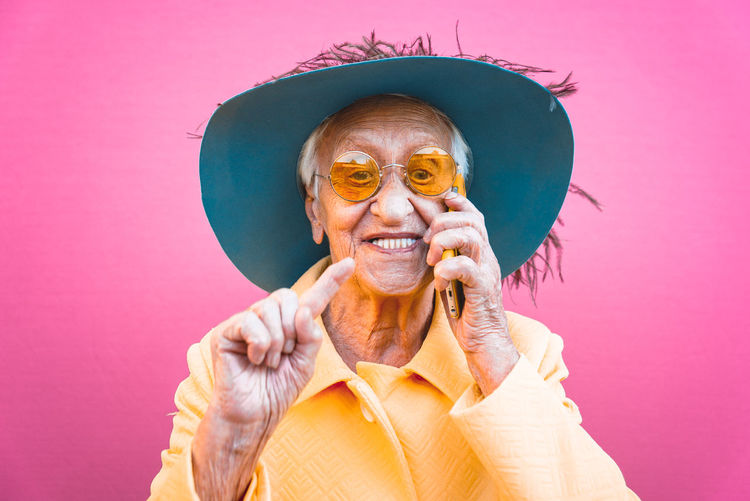 Senior woman wearing hat talking over smart phone against pink background