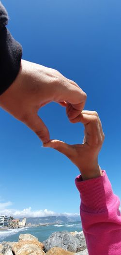 Close-up of hand holding umbrella against clear blue sky