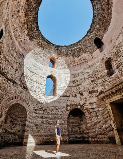 Man standing inside ancient roman building with natural light shining on him.