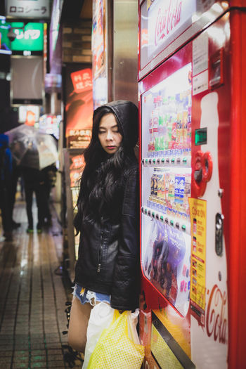 Mid adult woman wearing raincoat standing by display cabinet in city at night