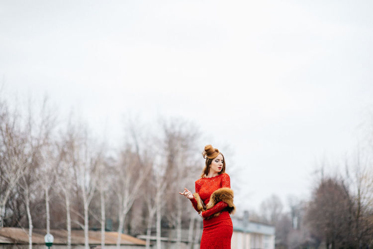 Portrait of woman standing against sky