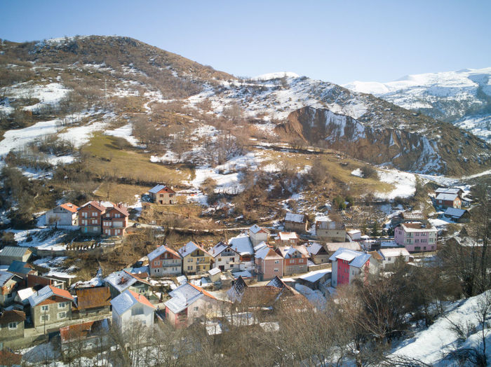 High angle view of townscape and snowcapped mountains
