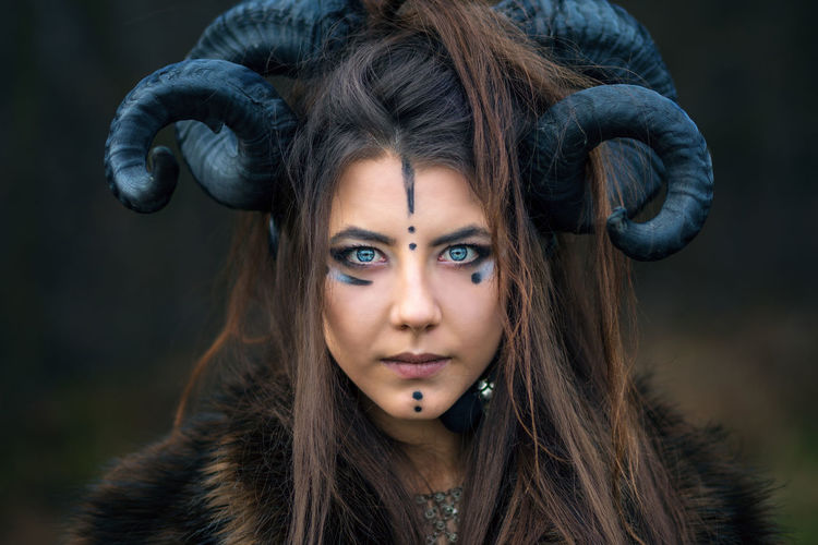 Close-up portrait of serious woman with painted face wearing horns