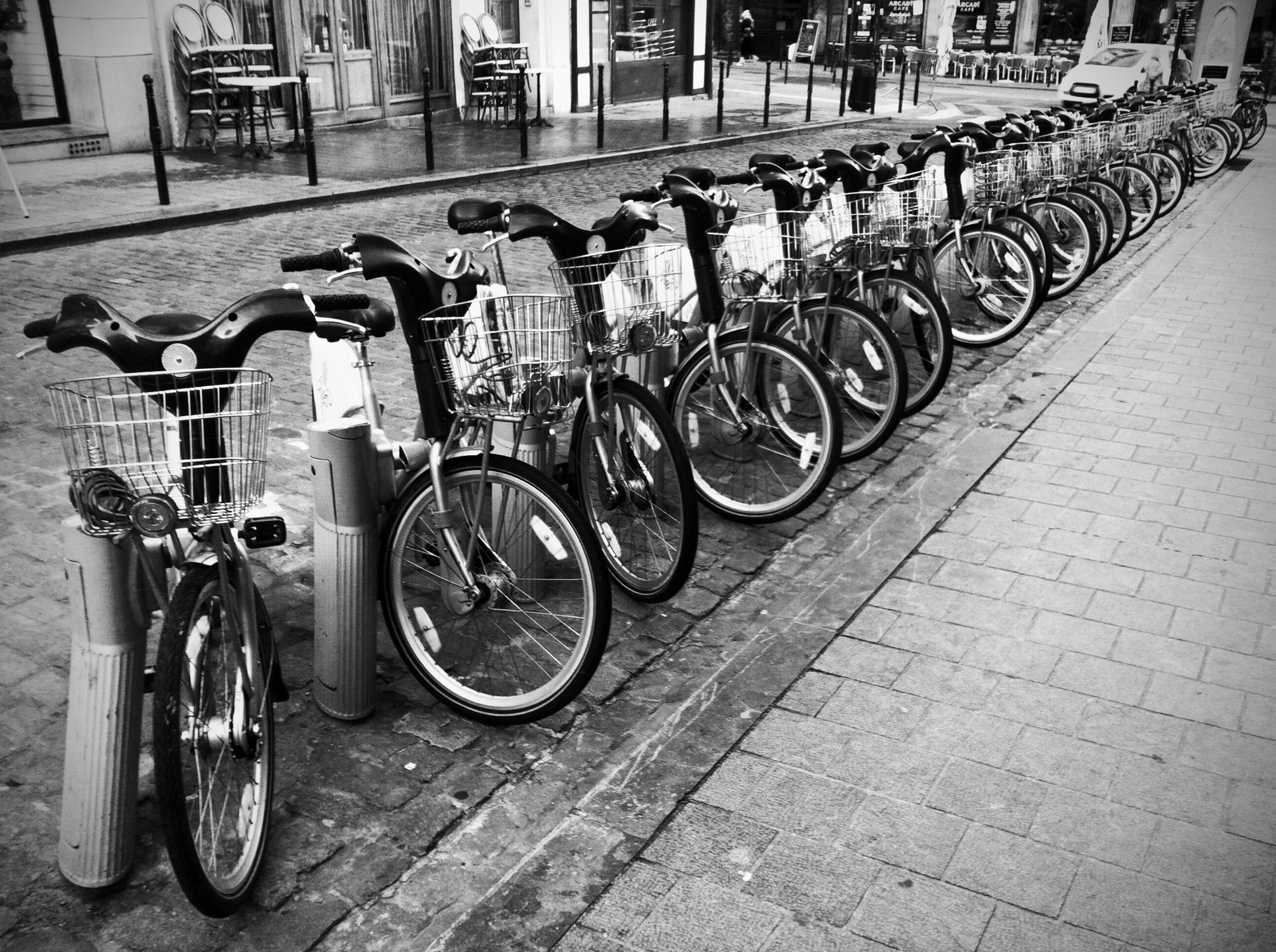 bicycle, transportation, mode of transport, land vehicle, parked, stationary, parking, street, built structure, architecture, building exterior, sidewalk, in a row, outdoors, wheel, day, railing, city, parking lot, travel