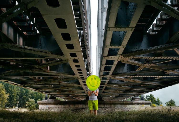 Front view of man with balloon standing under railway bridge