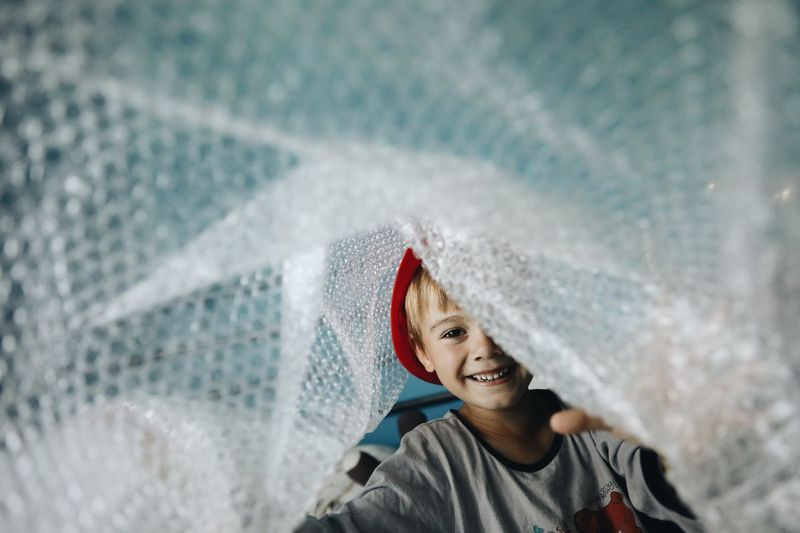 Portrait of boy playing with bubble wrap