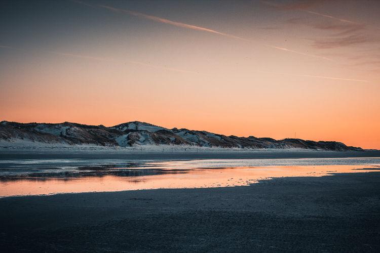 Sunset by the sea Seascape Sky Water Sunset Sea Orange Color Beach Outdoors No People Non-urban Scene Orange Sky Calm Dunes Dune