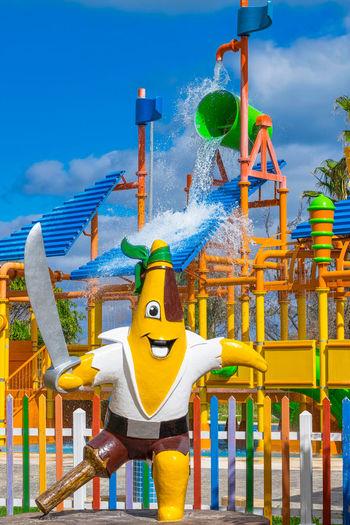 Yellow amusement park ride against blue sky