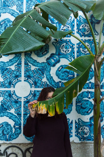 Portrait of woman holding banana leaf by patterned wall