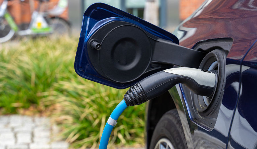 Electricity  Alternative Alternative Energy Car Technology Charging Charging Electric Car Electric Car Focus On Foreground Day Land Vehicle Mode Of Transportation Transportation Close-up No People Black Color Outdoors Nature Motor Vehicle Plant Metal Refueling Blue Wheel Vehicle Part Stationary