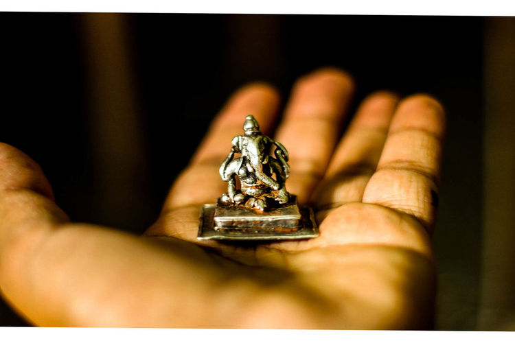 Close-up of hand holding ganesha figurine at home